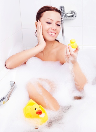 beautiful young brunette woman taking a relaxing bath with foam and playing with toy ducks photo