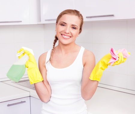 beautiful  young housewife wearing gloves and holding detergent,  in the kitchen at home Stock Photo - 12282802