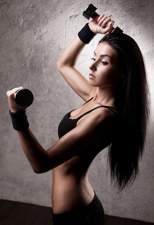 petite: high contrast portrait of a  beautiful young woman working out with dumbbells in the gym