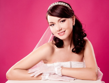 beautiful happy bride, sitting by the table,  isolated against pink studio background photo