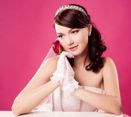 beautiful happy bride, sitting by the table and holding a rose,  isolated against pink studio background Stock Photo - 12713081
