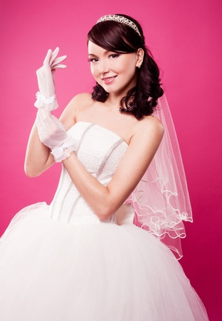 beautiful happy bride putting on gloves, isolated against pink studio background photo