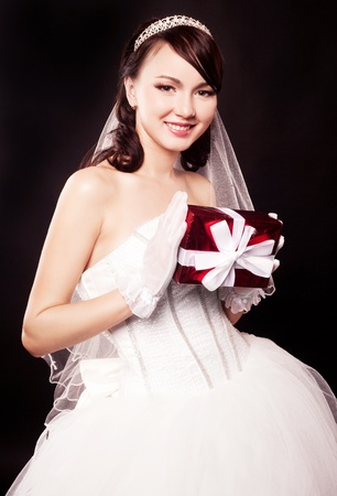 beautiful young bride with a present, isolated against black studio background photo
