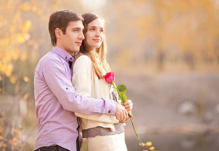 happy young couple spending time outdoor in the autumn park (focus on the man) photo