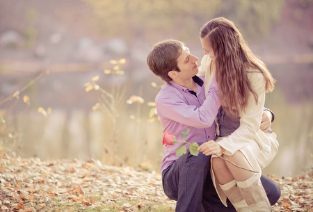 low contrast portrait of a happy young couple embracing and kissing outdoor in the autumn park (focus on the man) photo