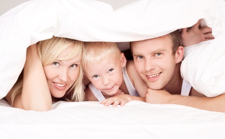 happy family: mother ,father and their son under the blanket  in bed at home Stock Photo - 12714089