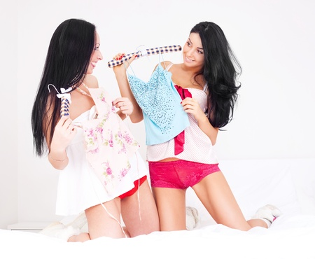 two beautiful brunette women choosing clothes in the bedroom at home photo
