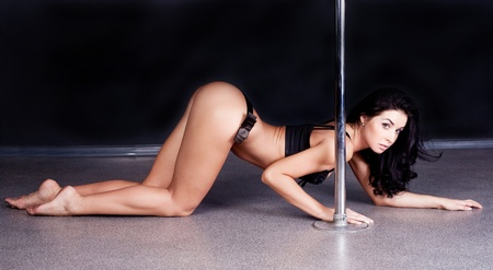 Young sexy pole dance woman against dark background  Stock Photo - 12714326