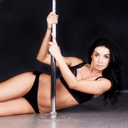 Young sexy pole dance woman against dark background  photo