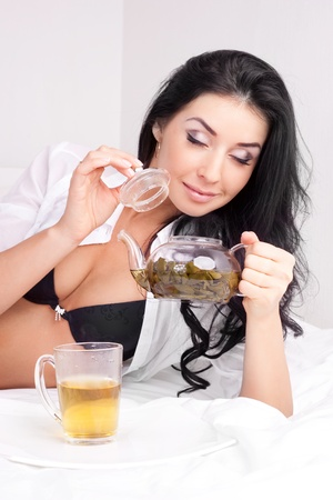 sexy brunette woman drinking green tea in bed at home photo