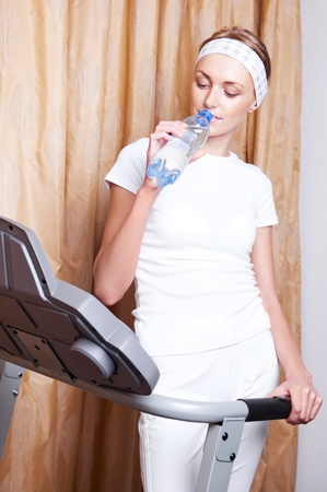 beautiful young blond woman drinking water after working out on the racetrack at home Stock Photo - 12714378
