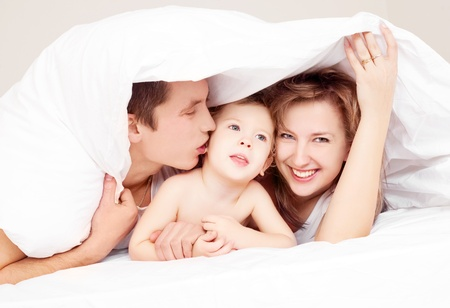 happy family; mother ,father and their baby under the blanket on the bed at home photo