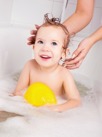 mother washing her baby in the bath with foam  photo