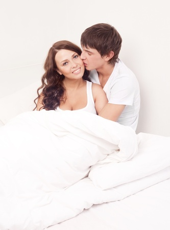 happy young beautiful couple under the blanket in bed at home photo