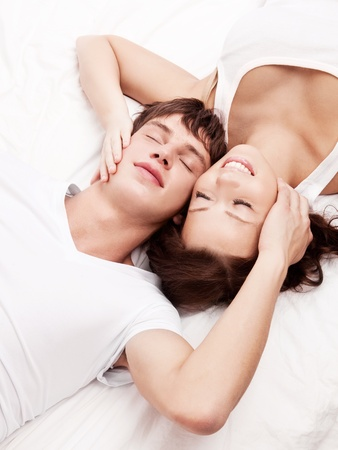 insides: happy young beautiful couple in bed at home, top view