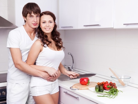 happy young loving couple cooking together in the kitchen at home Stock Photo - 12714377