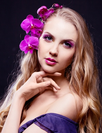 beautiful young woman with long curly hair and an orchid, isolated against black studio background photo