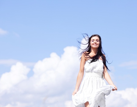 woman flying: beautiful young brunette woman outdoor on a summer day, against blue sky with clouds