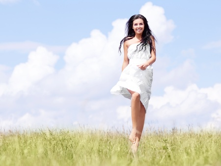 beautiful young brunette woman outdoor on the hill on a summer day, against blue sky with clouds photo