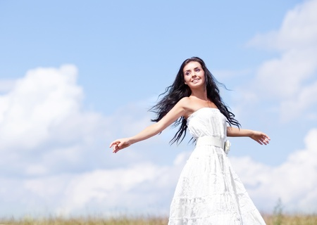 beautiful young brunette woman outdoor on the hill on a summer day, against blue sky with clouds Stock Photo - 12714397
