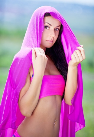 piercing: beautiful young brunette oriental beautiful woman, wearing pink clothes and a shawl outdoor on a summer day