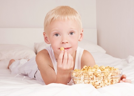 six year old boy boy eating popcorn in bed at home photo