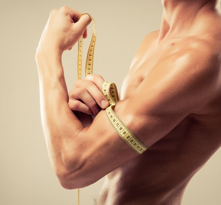 male torso: young muscular man measuring the size of his biceps,   isolated on brown studio background