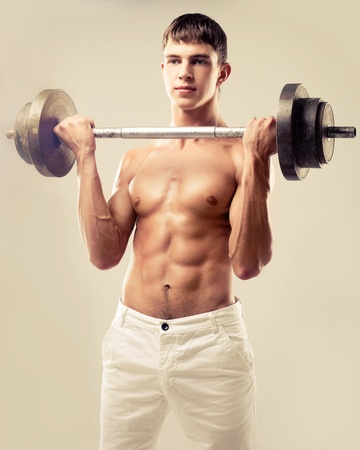 young muscular man with a bar, isolated on brown studio background photo