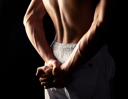 arms and back of a young muscular man, isolated against black studio background photo