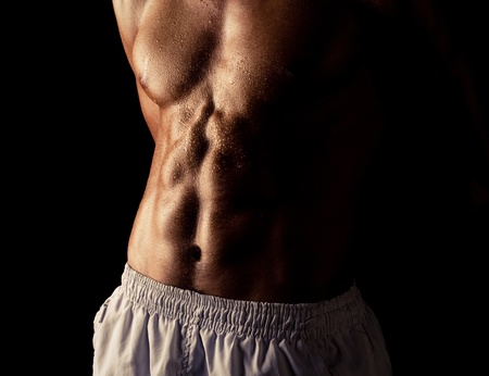 torso of young muscular man, isolated on black background photo