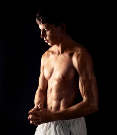 wet body: young muscular man, isolated on black background