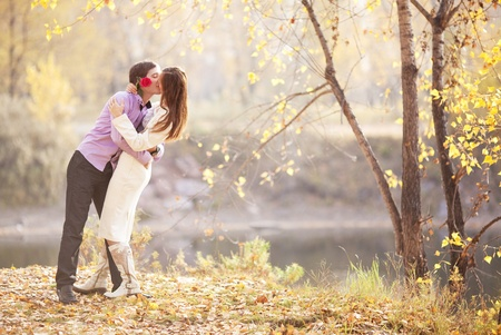 romantic kiss: happy young couple kissing outdoor in the autumn park