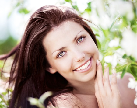 beautiful young brunette woman with the apple tree on a warm summer day photo