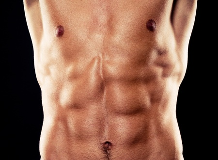 muscle belly: torso of young muscular man, isolated on black background Stock Photo