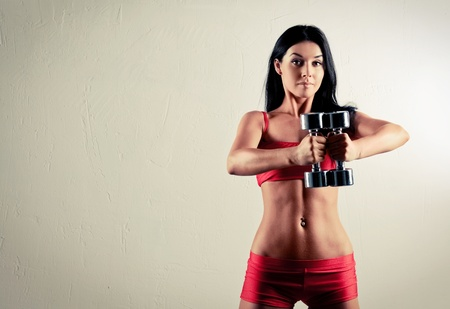 high contrast studio portrait of a beautiful sporty muscular woman working out with two dumbbells, copyspace to the left photo
