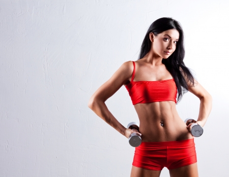 girl fitness: high contrast studio portrait of a beautiful sporty muscular woman working out with two dumbbells, copyspace to the left Stock Photo