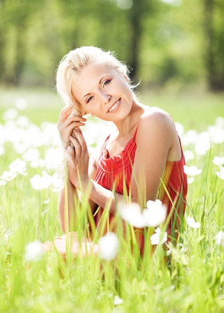 beautiful young blond woman  on the  meadow with white flowers  on a warm summer day photo
