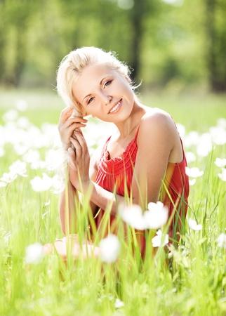 belle jeune femme blonde sur le pr� avec des fleurs blanches sur une chaude journ�e d'�t� photo
