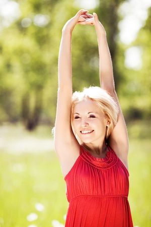 happy young blond woman stretching to the Sun on a warm summer day photo
