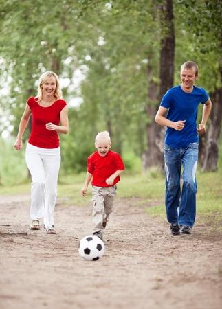 jugando futbol: joven familia feliz jugando al fútbol al aire libre en un día de verano (se centran en el niño)