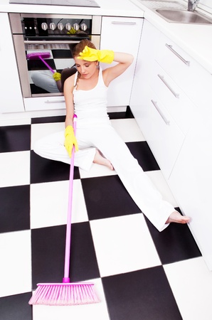 tired unhappy  housewife  holding a broom  in the kitchen at home Stock Photo - 12714402
