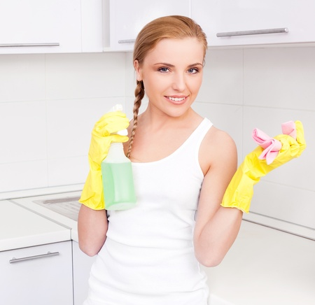 beautiful  young housewife wearing gloves and holding detergent,  in the kitchen at home