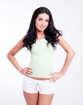 petite: beautiful young slim brunette woman against studio background