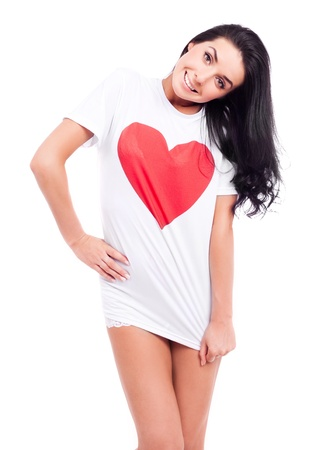 beautiful young woman wearing a  shirt with a big red heart, isolated against white background photo