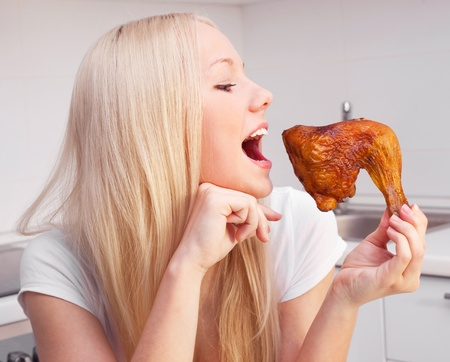 beautiful young blond woman eating chicken in the kitchen at home photo
