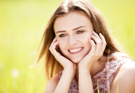 outsides: beautiful happy young woman  in the park  on a warm summer day