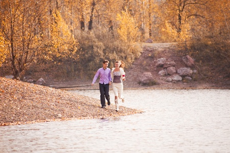 happy young couple having fun and running outdoor in the autumn park  photo