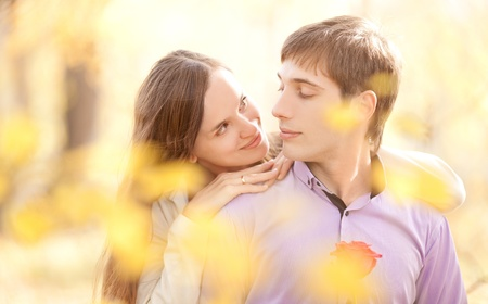 tender passion: happy young couple outdoor in the autumn park (focus on the man)
