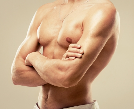 torso of a young muscular man, isolated on brown studio background photo