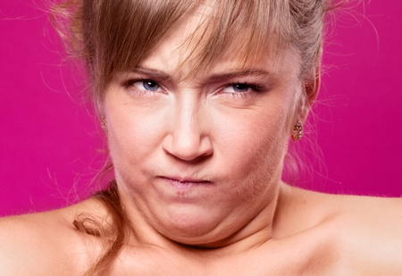 tense: humorous portrait of an angry young woman, isolated against purple studio background